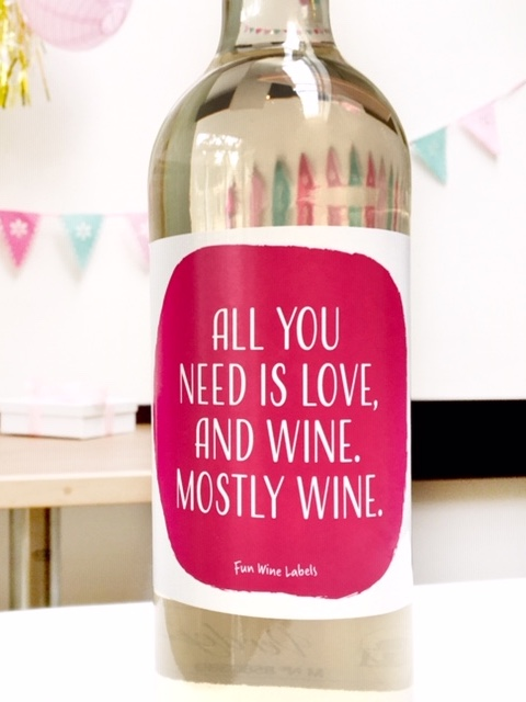 Quote op sticker; All you need is love, and wine, mostly wine. op een fles wijn